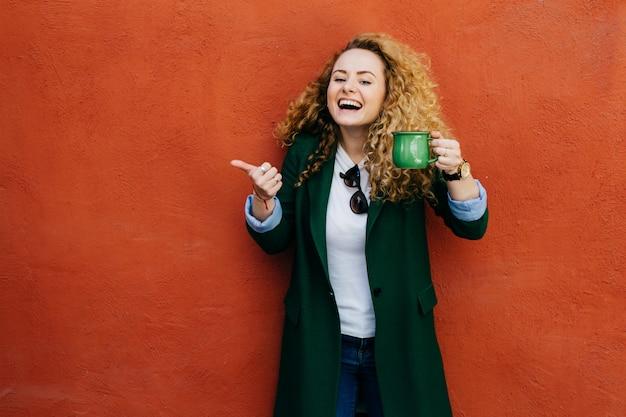 Mulher excitada com cabelo loiro encaracolado, vestindo jaqueta segurando a xícara de café verde, levantando o polegar.