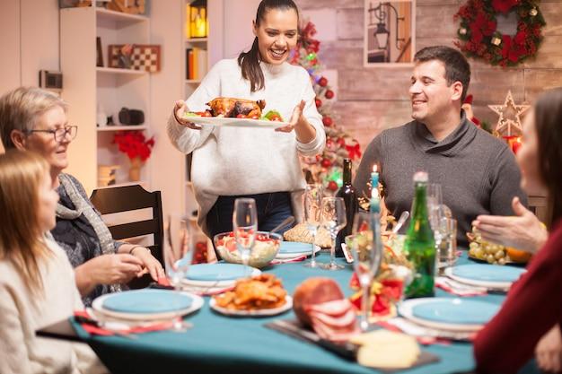 Mulher excitada com frango delicioso no jantar de natal em família.