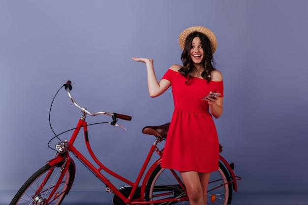 Mulher excitada com o telefone na mão, em pé ao lado de sua bicicleta. menina morena emocional com chapéu de palha, posando na frente da bicicleta.