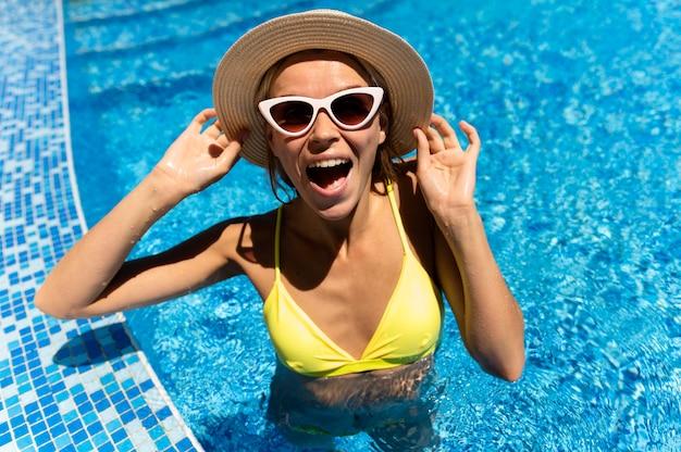 Mulher excitada com óculos de sol na piscina