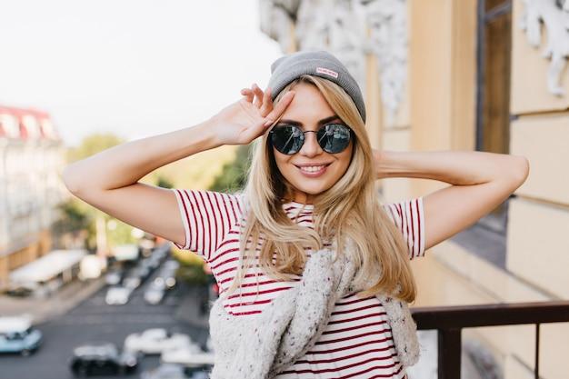 Mulher excitada com óculos escuros posando na varanda com as mãos ao alto e rindo para a câmera