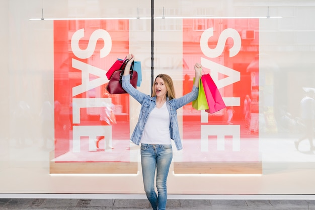 Mulher excitada com sacolas coloridas, levantando os braços
