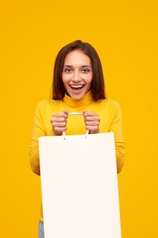 Mulher excitada com uma sacola de compras em branco