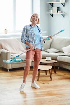 Mulher excitada, desfrutando de tarefas domésticas