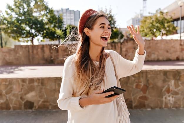 Mulher excitada em casaco de lã, posando na rua. menina atraente de cabelos compridos na boina vermelha, acenando com a mão.