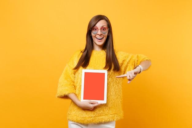 Mulher excitada em copos de coração apontando o dedo indicador no computador tablet pc com tela vazia preta em branco isolada no fundo amarelo brilhante. pessoas sinceras emoções, estilo de vida. área de publicidade.