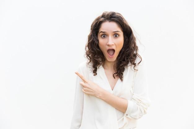 Mulher excitada espantada com a boca aberta, apontando o dedo
