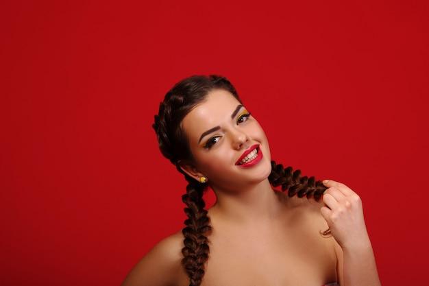 Mulher excitada feliz olhando para o lado gritando alegre com vento no cabelo na parede vermelha. modo feminino caucasiano multirracial bonito
