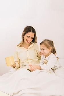 Mulher excitada lendo livro com a filha na cama