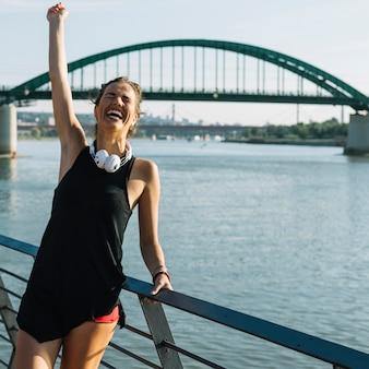 Mulher excitada levantando os braços na frente do rio