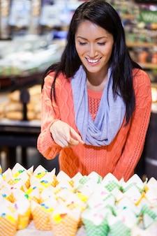 Mulher excitada olhando para cupcakes