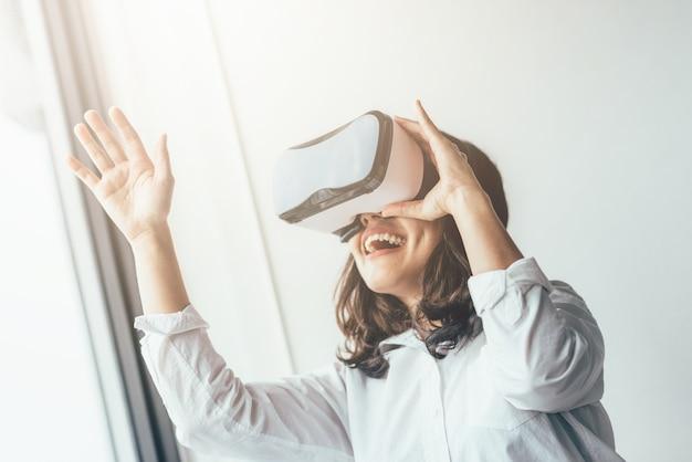 Mulher excitada se divertindo usando fone de ouvido de realidade virtual