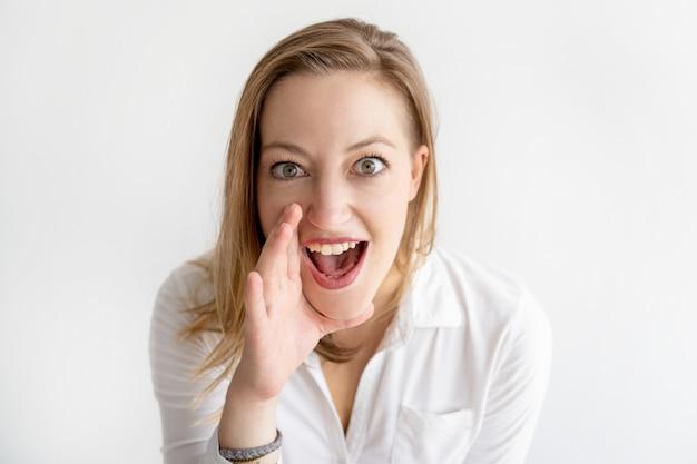 Mulher excitada segurando a mão perto da boca e gritando alto