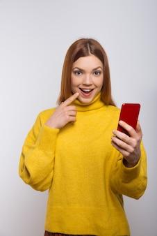 Mulher excitada segurando o smartphone e olhando