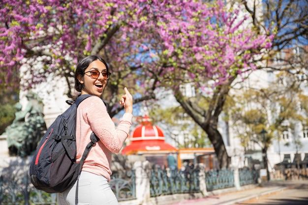 Mulher excitada usando mochila e apontando para a árvore florescendo