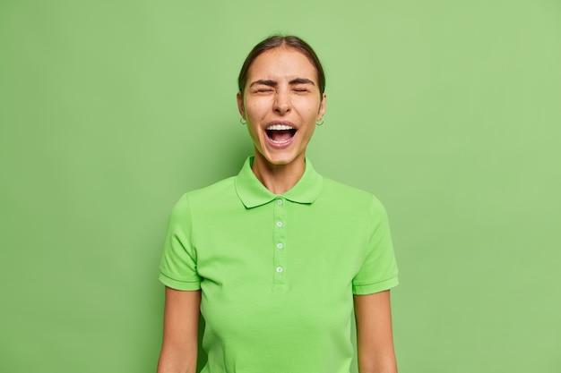 Mulher exclama com os olhos fechados e grita com as emoções mantém a boca bem aberta vestida com uma camiseta casual em verde brilhante espantada com as notícias