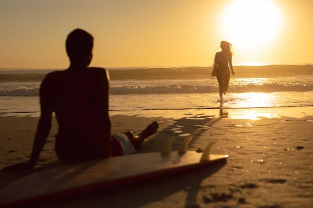 Mulher, executando, com, surfboard, enquanto, homem, relaxante, praia