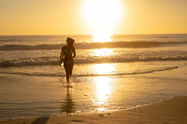 Mulher, executando, com, surfboard, praia
