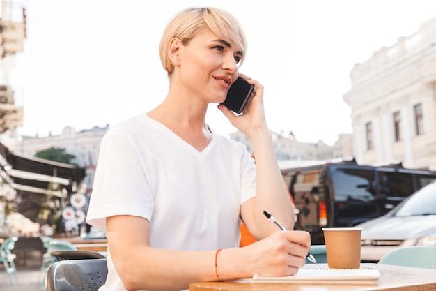 Mulher executiva caucasiana, vestindo uma camiseta branca, sentada em um café de verão ao ar livre, enquanto escreve no caderno e fala no celular
