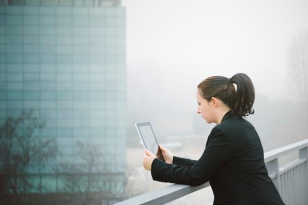 Mulher executiva, ler e-mails em seu tablet suportado em uma grade com edifício de escritórios eu