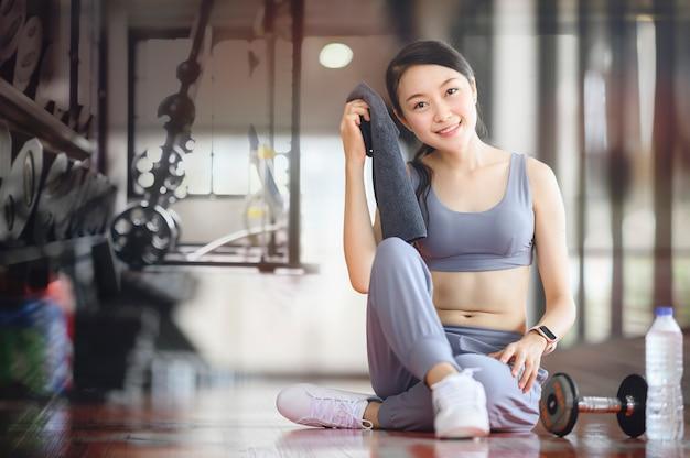 Mulher, exercício, malhação, em, ginásio, aptidão, quebrar, relaxe, segurando toalha, sorrindo, e, olhando câmera