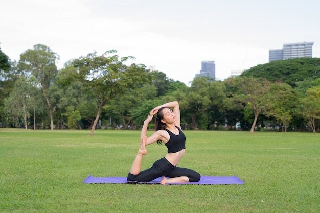 Mulher exercita ioga no parque pronta para um estilo de vida saudável na natureza