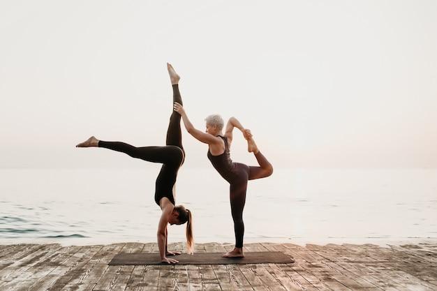 Mulher exercitando acro yoga na praia perto do mar pela manhã com o tutor feminino maduro