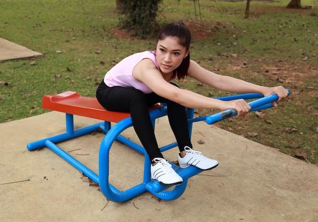 Mulher exercitando com equipamento de exercício no parque público