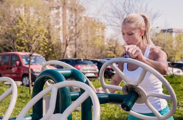 Mulher exercitando com equipamento de ginástica no parque público. conceito de esporte e estilo de vida - fitness woman working