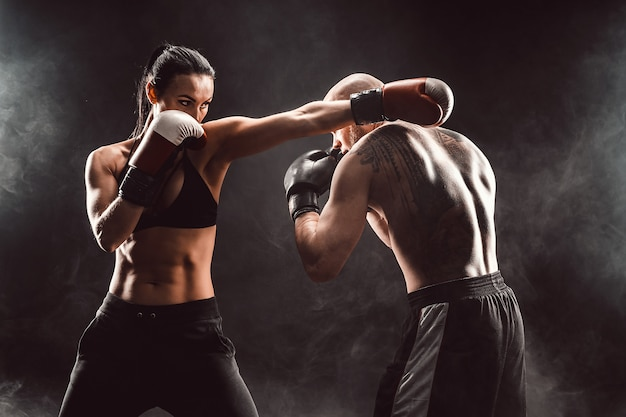 Mulher exercitando com treinador na aula de boxe e defesa pessoal luta feminina e masculina
