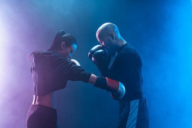 Mulher exercitando com treinador na aula de boxe e defesa pessoal