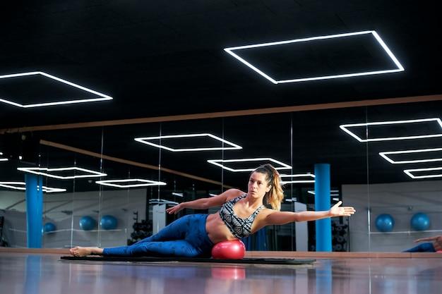 Mulher exercitando exercícios de bola de fitness de pilates em um ginásio moderno.