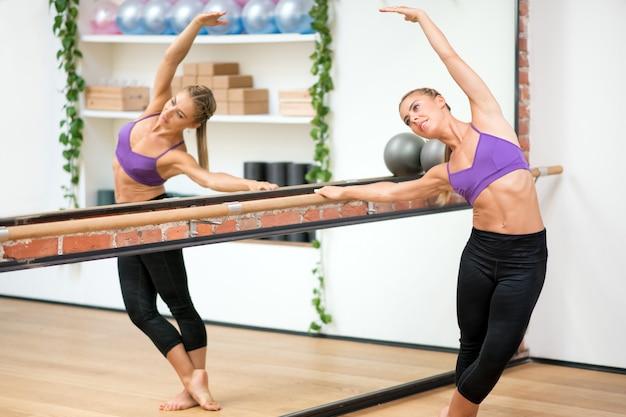 Mulher, exercitar, barra lateral, esticar, em, ginásio