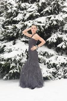 Mulher exótica com cabelo curto, retrato de estilo de beleza. mulher careca sorridente, fofa e pensativa no inverno, no contexto da neve e longos pinheiros cobertos de neve. mulher posando em vestido de noite