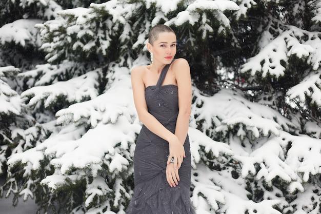 Mulher exótica com cabelo curto, retrato de estilo de beleza. sorridente, fofa e pensativa mulher careca no inverno no contexto da neve e longos pinheiros cobertos de neve. mulher posando em vestido de noite