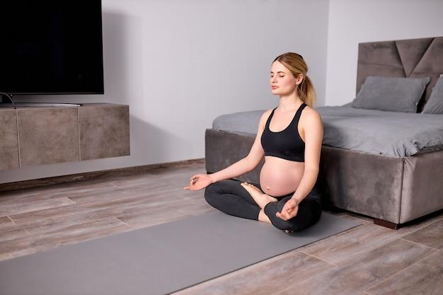 Mulher expectante feliz e relaxada em uma roupa esportiva preta sentada no chão meditando
