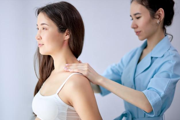 Mulher expectante morena recebendo massagem no pescoço e ombros por massagista feminina