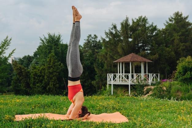 Mulher experiente em ioga se sentindo calma e livre enquanto pratica a postura perfeita para a cabeça.