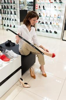 Mulher experimenta sapatos cremosos, vermelhos e mostarda cores em uma loja