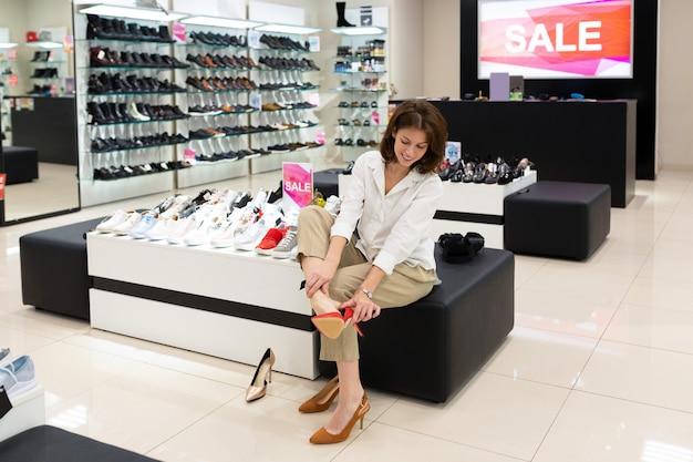 Mulher experimenta sapatos cremosos, vermelhos e mostarda em uma loja e pensa em sua escolha