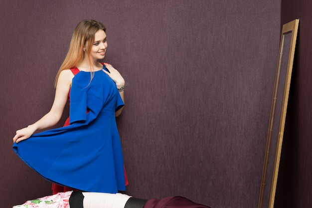Mulher experimenta um vestido perto do espelho.