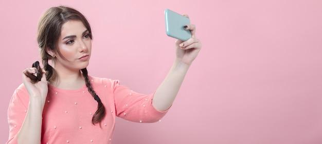 Mulher experimentando poses para selfie, mantendo o smartphone