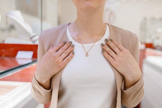 Mulher experimentando um colar de ouro em joalheria