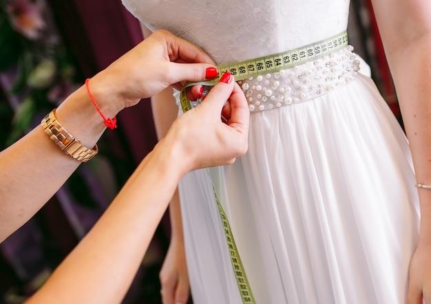 Mulher experimentando vestido de noiva em uma loja com assistente de mulheres.