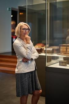 Mulher explorando exposições medievais em museu
