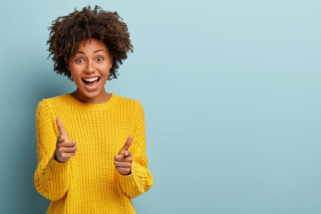 Mulher extrovertida e despreocupada com um afro posando com um suéter rosa