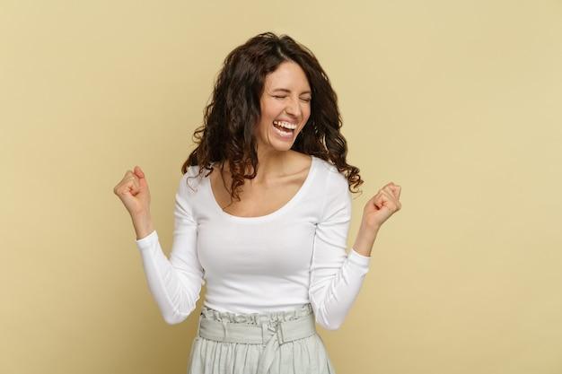 Mulher exultante em emoção de triunfo com sorriso dentuço olhos fechados cerrar os punhos celebrar o sucesso