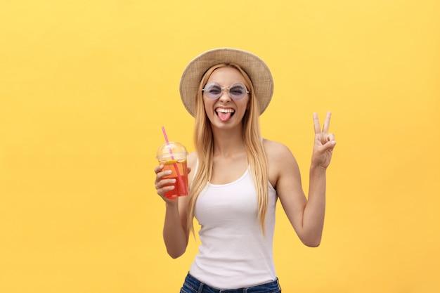 Mulher fabulosa em óculos de sol vestindo camiseta branca, mantendo o copo de suco isolado sobre o fundo amarelo
