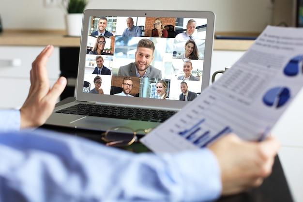 Mulher fala em videochamada com colegas em briefing online