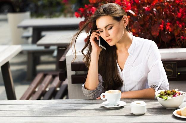 Mulher fala no telefone sentado à mesa em um restaurante